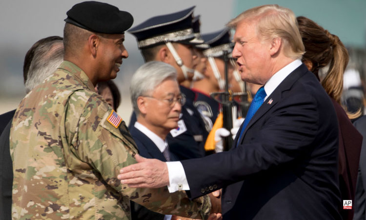 November 7, 2017 – U.S. President Donald Trump, right, is greeted by U.S. Forces Korea Commander General Vincent Brooks, left, as he arrives at Osan Air Base in Pyeongtaek.