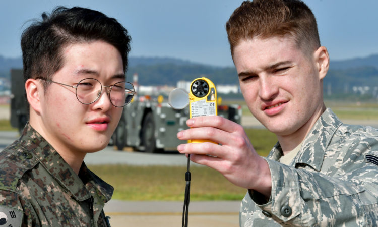 U.S. Air Force Staff Sgt. Jason Jones, 51st Operations Support Squadron weather forecaster, and Republic of Korea Air Force Airman 1st Class Choi, Min Jae, weather observer, gather weather information using a kestrel meter at Osan Air Base, Republic of Korea, Oct. 4, 2017. Members from the 51st OSS and RoKAF weather units have partnered together to help provide better forecast predictions to Osan AB personnel. (U.S. Air Force photo by Staff Sgt. Franklin R. Ramos/Released)
