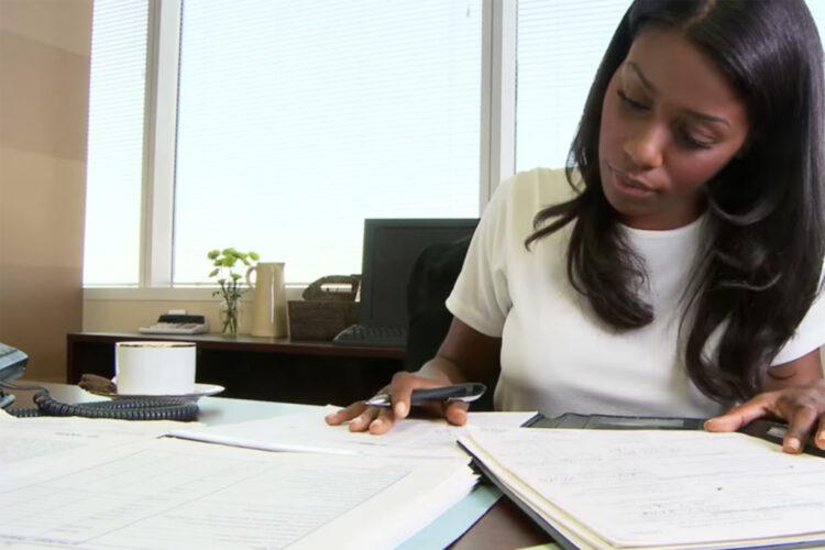 A woman working at a desk with papers and documents in front of her.