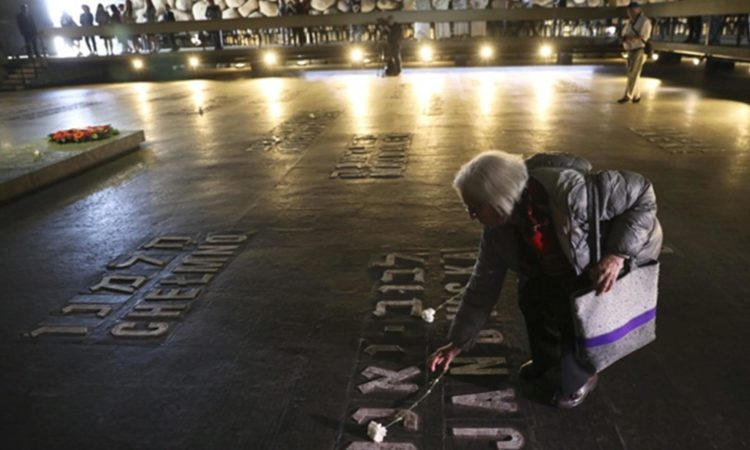 A woman lays a flower at the Yad Vashem Holocaust memorial on Remembrance Day. © AP Image