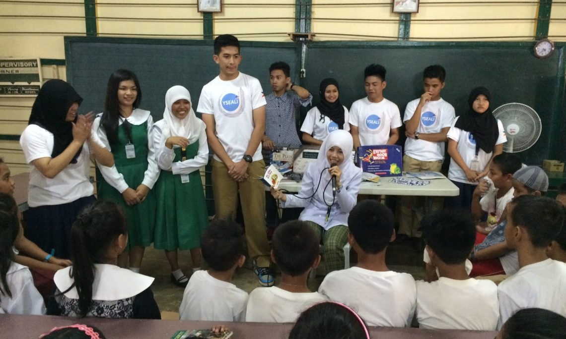U.S. government alumni read stories to elementary students in Jolo and encourage them to stay in school.