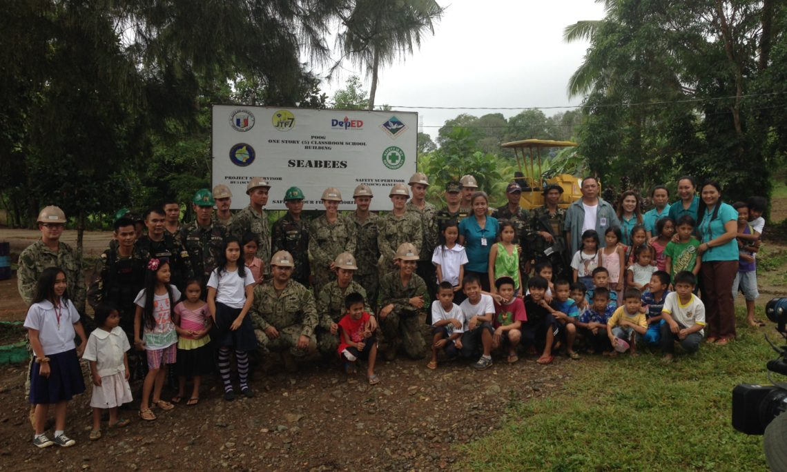 United States Navy Seabees, Philippine Army Engineers, and school teachers, and students from Poog Elementary School in Toledo City, Cebu, at the construction site of a new five-classroom school building. The U.S.-Filipino engineering team will complete this project, one of three in Cebu, by March 2015.