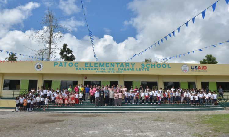 Patoc Elementary School students and teachers have their photo taken in front of their new classrooms, designed to withstand typhoons with wind speeds of up to 360kph.