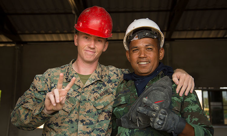 U.S. Marine Lance Cpl. Jonathon Couch, an electrician with Marine Wing Support Squadron 171, 1st Marine Aircraft Wing, poses for a photo with Royal Thai Army Sergeant Major First Class Tralrak Tongsomrld during an engineering civic action project as part of Exercise Cobra Gold 2020