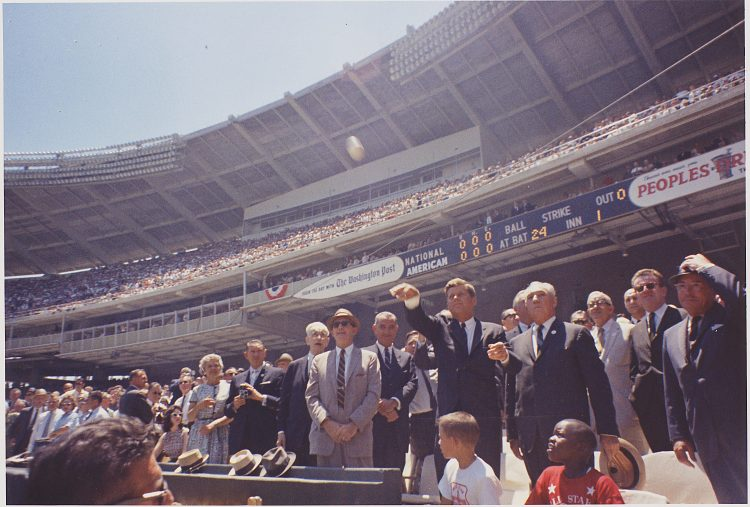 """President John F. Kennedy throws the first ceremonial pitch at the newly constructed """"D.C. Stadium"""" in Washington, DC."""