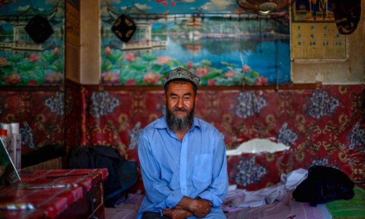 ชายชาวอุยกูร์ที่เมืองโฮตัน (Hotan) ในซินเจียงของจีน โฮตันอยู่ภายใต้การสังเกตการณ์ของเจ้าหน้าที่ตำรวจอย่างใกล้ชิด เหมือนเช่นเมืองอื่นๆ อีกมากมายที่มีชาวอุยกูร์อาศัยอยู่ (© Elizabeth Dalziel/AP Images)