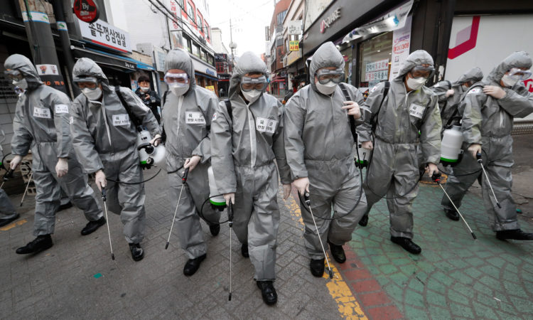 Line of people wearing protective suits spraying city streets (© Ahn Young-joon/AP Images)