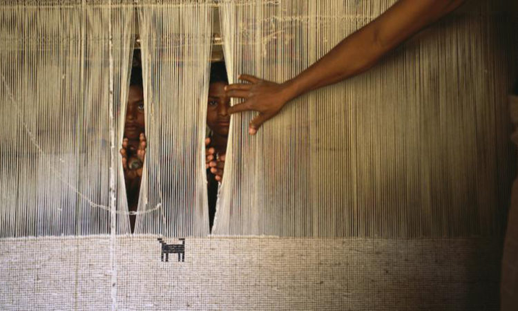 Children forced to work in a textile factory peer from behind a loom in Uttar Pradesh, India.